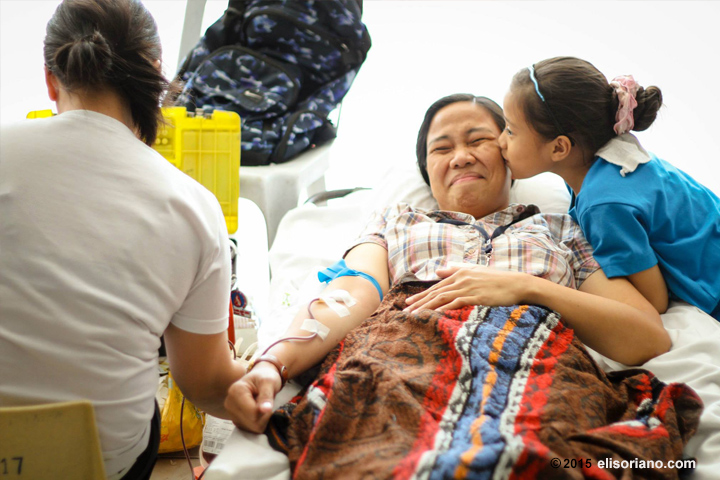 A member of the Church of God International is kissed by her daughter as she donates her blood in MCGI's blood donation drive at the ADD Convention Center in Pampanga, Philippines.